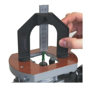 A person holding pieces of a router table to measure